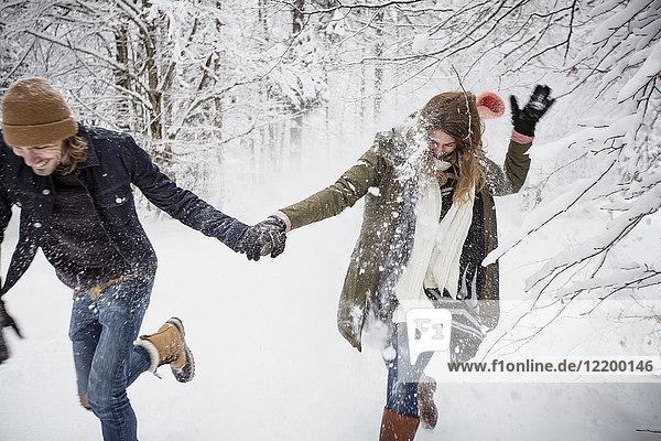 Glückliches Paar beim Laufen im Winterwald
