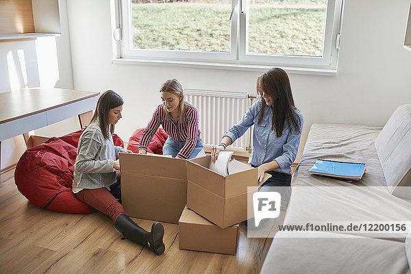 Drei junge Frauen beim Auspacken von Kartons im Zimmer