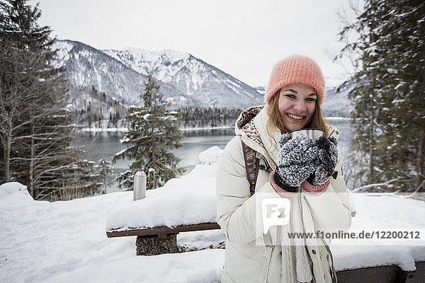 Porträt einer lächelnden jungen Frau in alpiner Winterlandschaft mit See