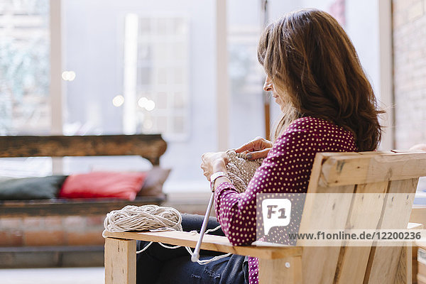 Frau sitzend auf dem Stuhl strickend