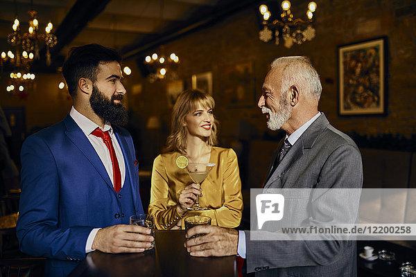 Zwei elegante Männer und Frauen  die sich in einer Bar treffen.
