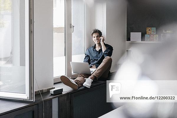 Lächelnder junger Mann am Telefon sitzend mit Laptop auf Fensterbank im Loft