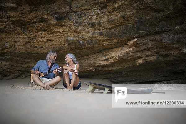 Schönes älteres Paar  das am Strand sitzt und Gitarre spielt.
