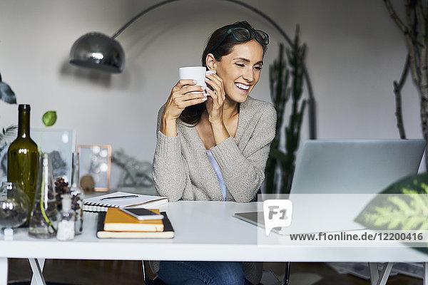 Glückliche junge Frau zu Hause mit Laptop auf dem Schreibtisch