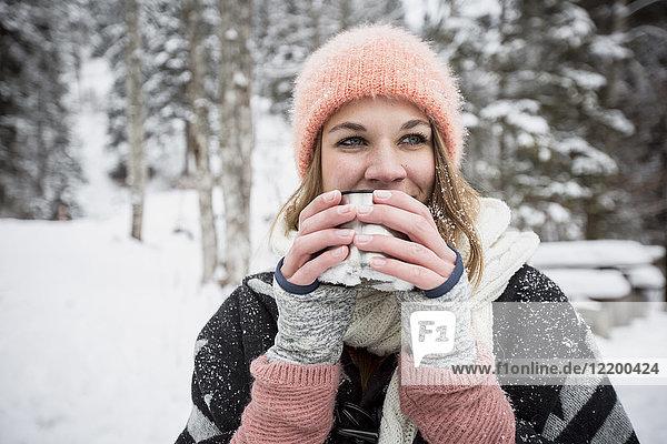 Porträt einer jungen Frau  die im Winter ein heißes Getränk im Freien trinkt.