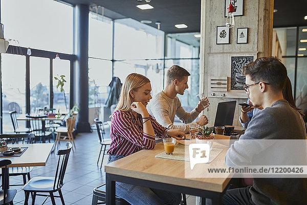Gruppe von Freunden sitzen zusammen in einem Cafe mit Laptop und Getränken