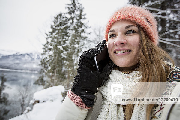 Portrait of smiling young woman on cell phone in alpine winter landscape