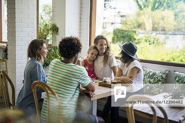 Fröhliche Freunde mit Kindern im gemütlichen Café