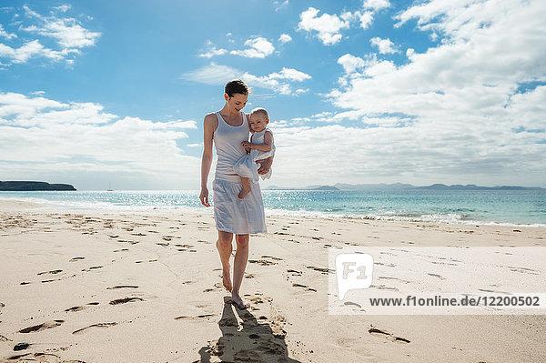 Mutter geht mit kleiner Tochter am Strand spazieren