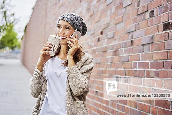 Porträt der glücklichen Frau mit Kaffee zum Telefonieren