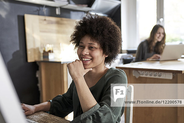 Happy young woman using computer in modern office