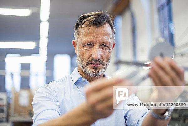 Reife Geschäftsleute in der Fabrik prüfen Komponente