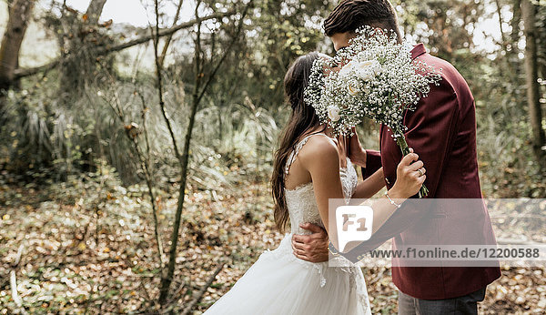 Unrecognizable bride and groom kissing in forest behind bouquet of flowers