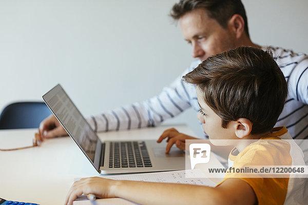 Vater und Sohn bei Tisch mit Junge mit Laptop