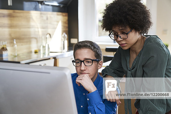 Two colleagues looking at computer monitor in office