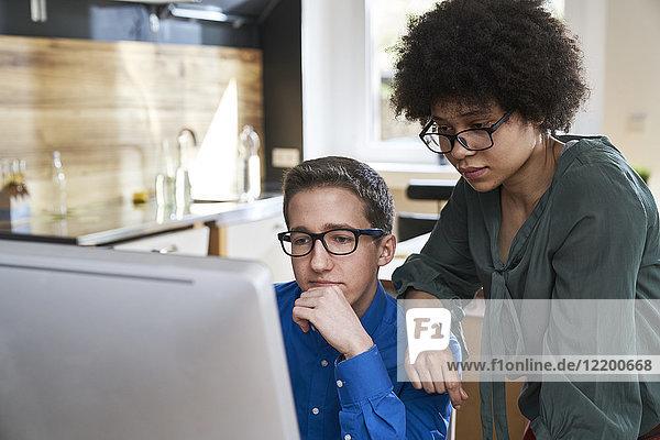 Zwei Kollegen beim Blick auf den Bildschirm im Büro