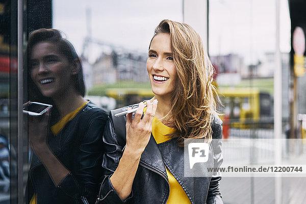 Porträt einer lachenden Frau am Telefon
