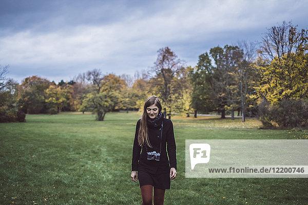 Junge Frau mit Kamera läuft auf einer Wiese im Herbstpark