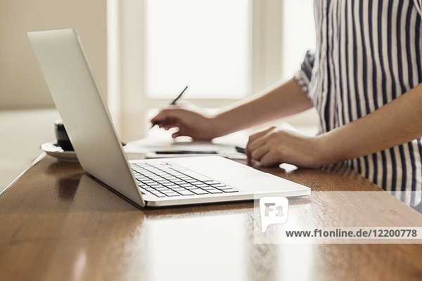 Nahaufnahme der Frau mit Laptop und Dokumenten auf dem Tisch zu Hause