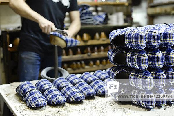 Nahaufnahme des Schuhmachers bei der Arbeit an Hausschuhen in der Werkstatt Nahaufnahme des Schuhmachers bei der Arbeit an Hausschuhen in der Werkstatt