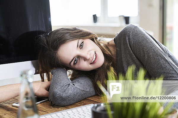 Portrait of smiling young woman leaning on desk in office