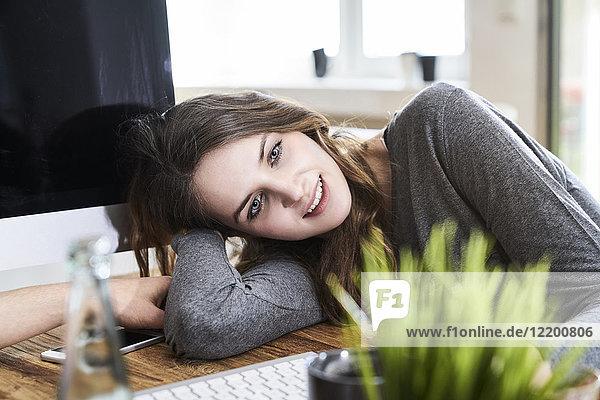 Porträt einer lächelnden jungen Frau  die sich im Büro auf den Schreibtisch lehnt.