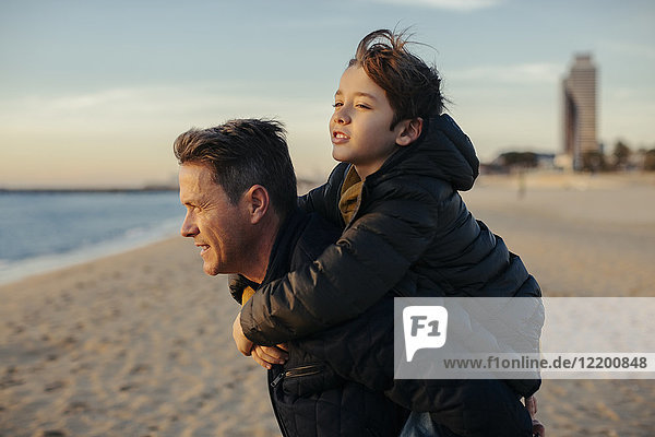 Father carrying son piggyback on the beach
