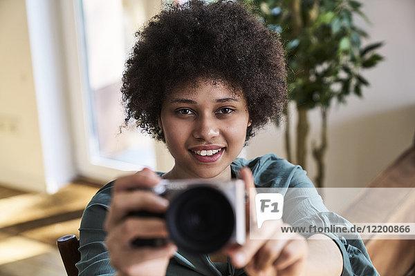 Porträt einer lächelnden jungen Frau mit Kamera