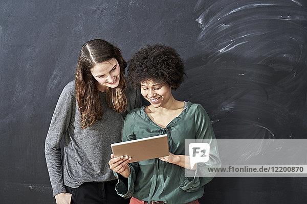 Zwei lächelnde junge Frauen teilen sich das Tablett vor der Tafel.
