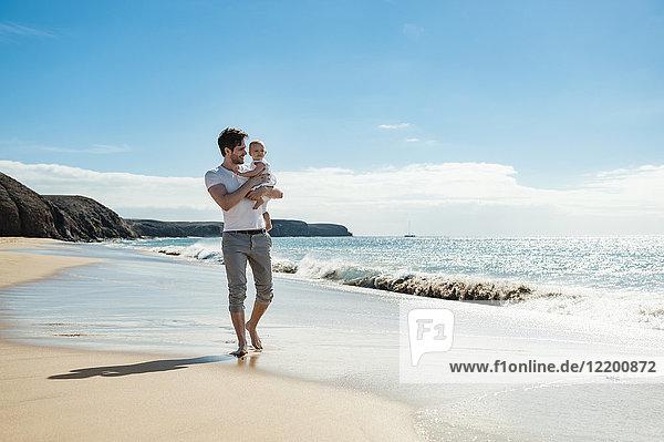 Spanien  Lanzarote  Vater mit seiner kleinen Tochter am Strand