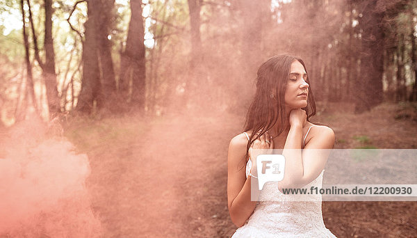 Woman with closed eyes wearing wedding dress in forest surrounded by clouds of smoke