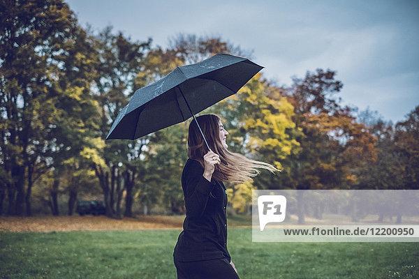 Fröhliche junge Frau mit Regenschirm beim Spaziergang im Herbstpark