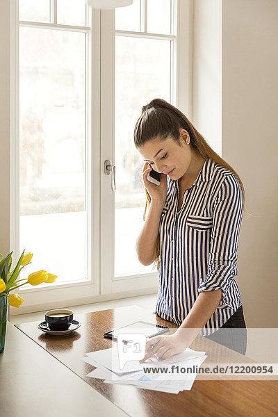 Junge Frau am Telefon bei der Arbeit an gedruckten Karten auf einem Tresen zu Hause
