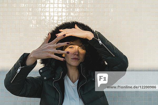 Porträt einer Frau mit Kapuzenjacke vor der gefliesten Wand