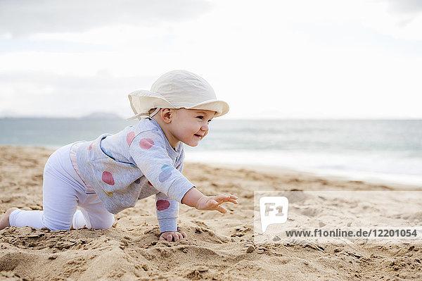 Spanien  Lanzarote  kleines Mädchen  das am Strand krabbelt