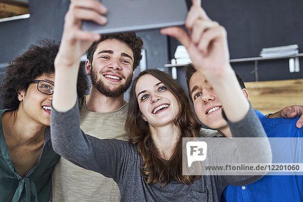 Lächelnde Mitarbeiter  die einen Selfie im Büro nehmen