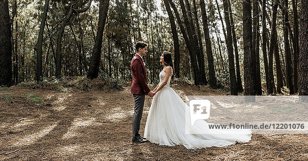 Bride and groom standing in forest holding hands