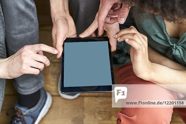 Four people sharing tablet