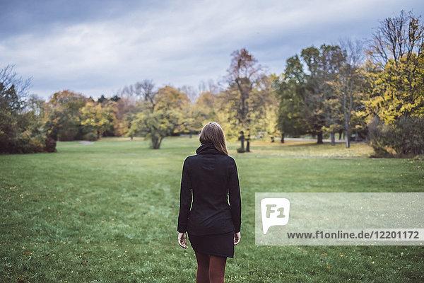 Rückansicht einer jungen Frau  die auf einer Wiese im Herbstpark spazieren geht.