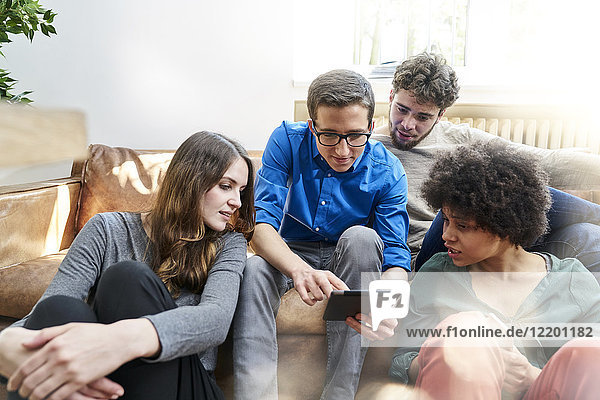 Young people sitting on sofa looking at tablet