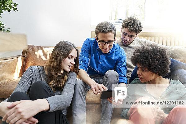 Junge Leute sitzen auf dem Sofa und schauen auf die Tafel.