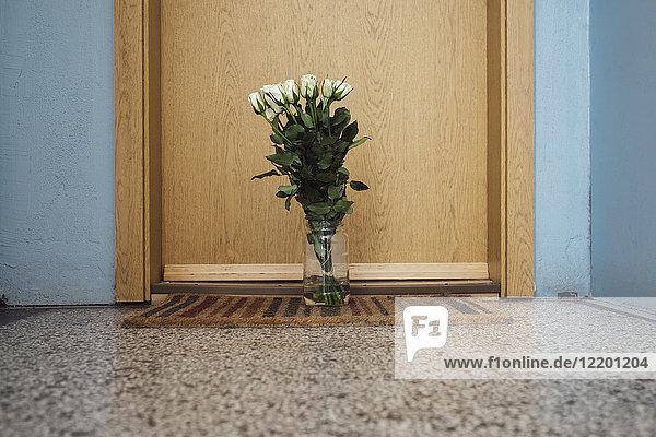 Vase mit Abschiedsblumen auf Fußmatte an der Wohnungstür des verstorbenen Nachbarn