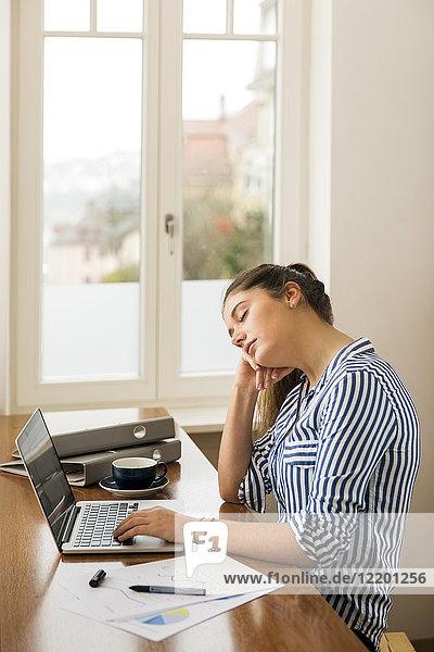 Junge Frau schläft zu Hause vor ihrem Laptop