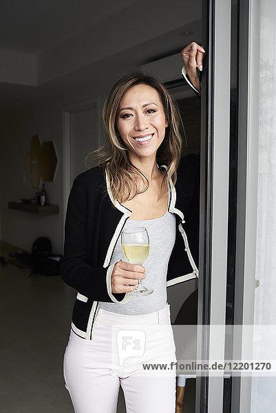 Porträt einer lächelnden Frau bei einem Glas Wein zu Hause