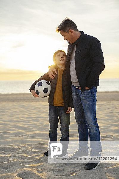 Vater umarmt Sohn mit Fußball am Strand bei Sonnenuntergang