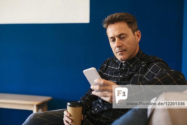 Geschäftsmann mit Kaffee zum Mitnehmen sitzend und auf dem Handy schauend