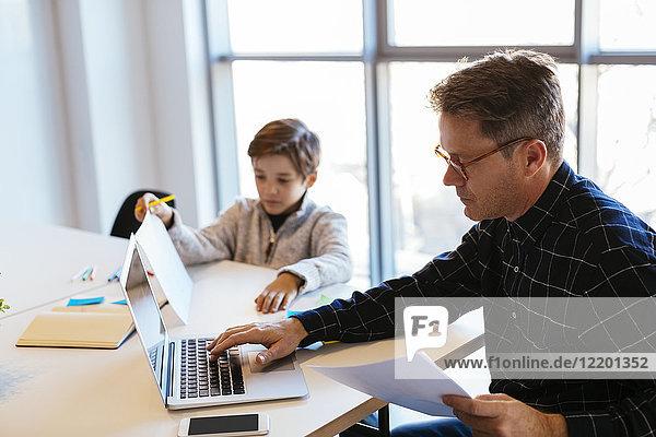 Geschäftsmann mit Laptop am Schreibtisch im Büro  neben ihm sitzt der Sohn