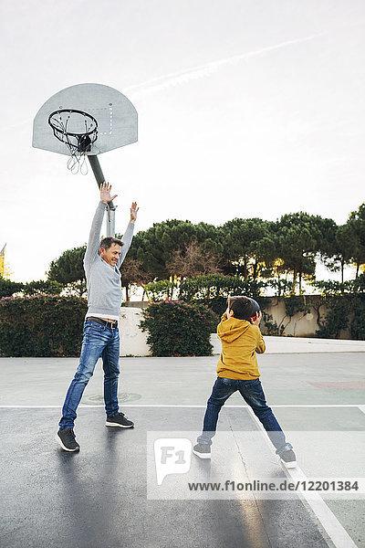 Vater und Sohn spielen Basketball auf einem Freigelände