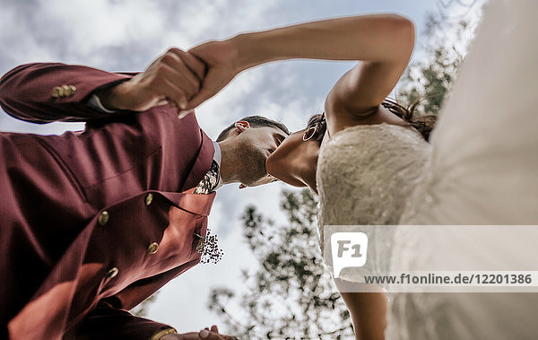 Bride and groom holding hands and kissing with sky in the background