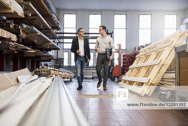 Zwei Geschäftsleute  die im Lagerraum der Fabrik spazieren und reden.